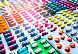 Pile of colorful medicine pills and capsules in blister packs, close up.