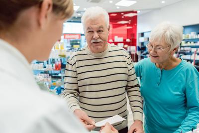 pharmacist getting prescription slip from senior couple